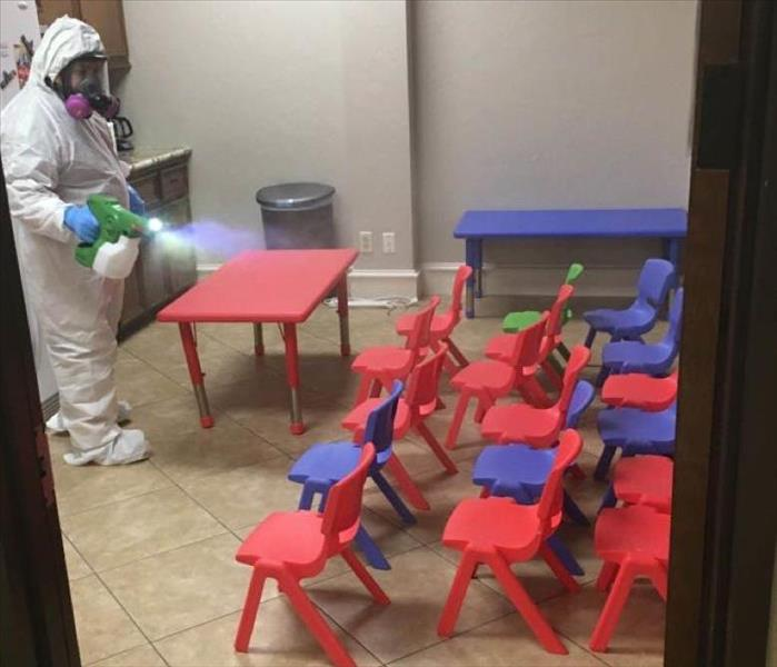 Person sprays disinfectant on daycare group of chairs.